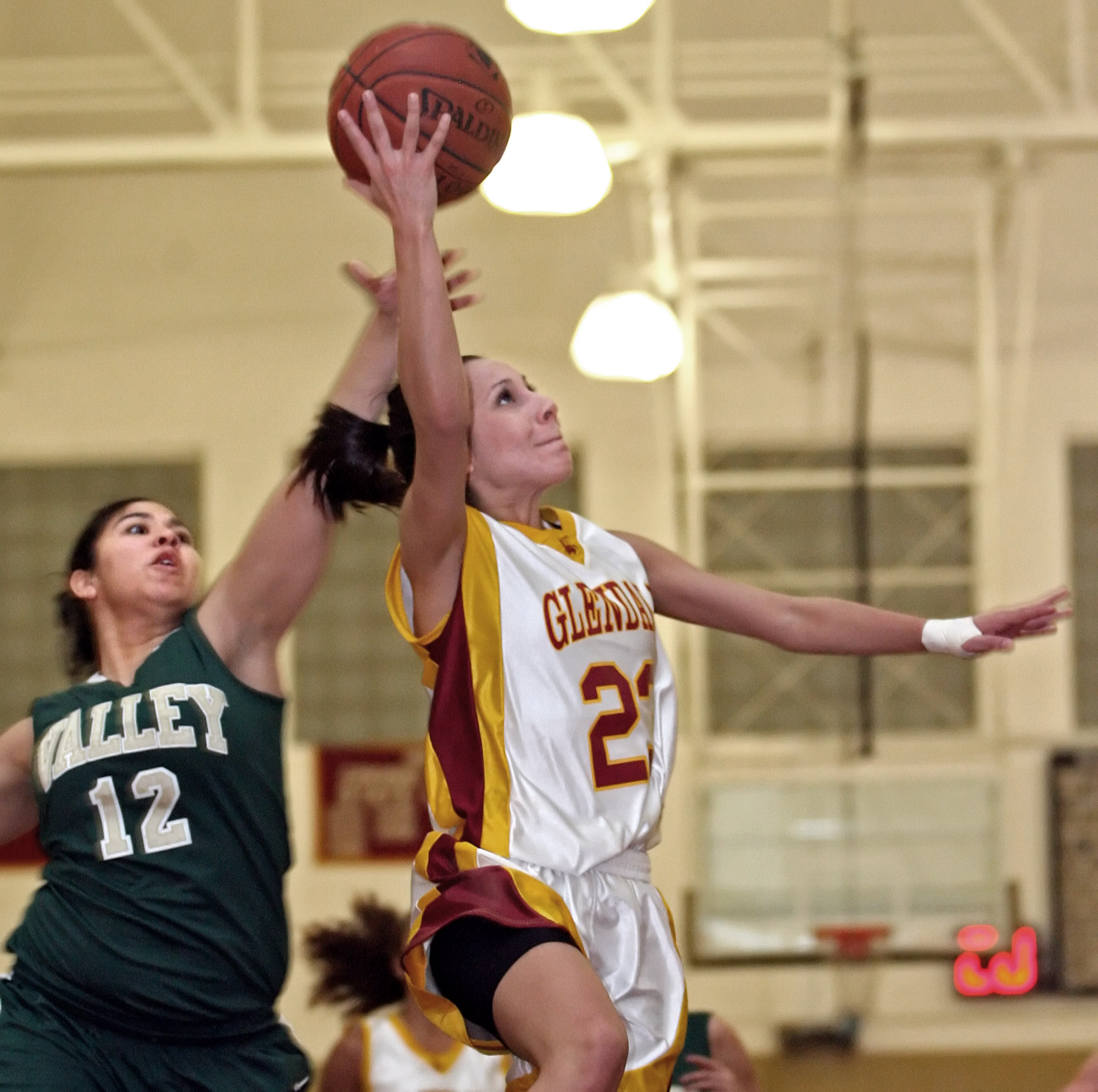 Glendale College women's basketball player #23 Susana Rascon gets fouled by L.A. Valley College player #12 Alejandra Gallardo as she takes it to the basket during first half action at the Vaqueros home in Glendale on Saturday, January 30, 2010.  (Raul Roa/News-Press)
